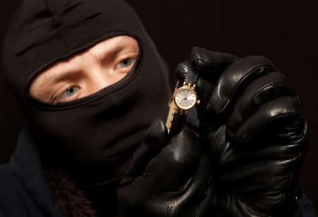 looting: Thief. Man in black mask with a golden watch. Focus on golden watch Stock Photo