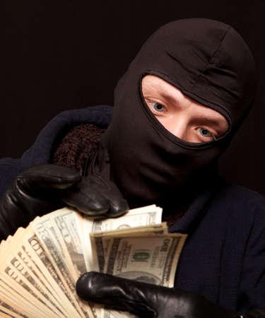 dinero falso: Ladrón y dinero en efectivo. Mostrando un ladrón contando el dinero Foto de archivo