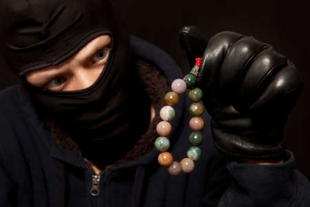 nephritis: Thief. Man in black mask with a jade necklace. Focus on necklace Stock Photo