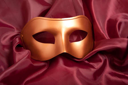 comedy tragedy: Golden carnival mask on red satin background  Stock Photo