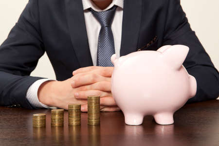 retirement fund: Businessman with pink piggy bank and coin