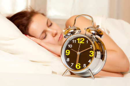 snooze: Sleeping woman resting in bed with alarm clock ready to wake her in the morning Stock Photo