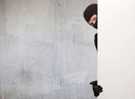 perpetrator: Ninja. Robber hiding behind a empty white sign with space for text