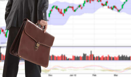 stock trader: Stock trader with a briefcase looking at monitors