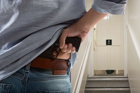 closet door: Bodyguard with gun protects client against an s water closet door background Stock Photo