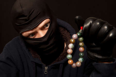 nephritis: Thief. Man in black mask with a jade necklace. Focus on thief