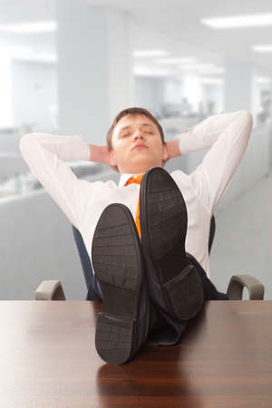sleeping businessman: Businessman sleeping. Businessman reclining with his feet up on desk in office