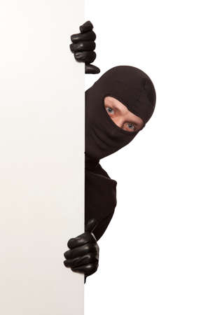 Ninja. Robber hiding behind a empty white sign with space for text. Isolated on white background