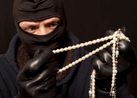 felon: Thief. Man in black mask with a pearl necklace. Focus on thief
