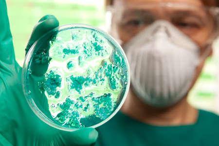 Científico que sostiene una placa de Petri con las células del virus