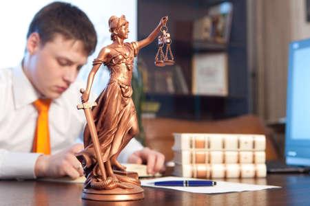 simbolo uomo donna: Statua della Giustizia e avvocato a leggere un libro in ufficio
