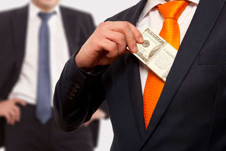 white collar crime: Businessman putting money in suit jacket pocket, concept for corruption, bribing