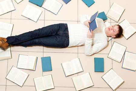 unreadable: Man reading a book, top view. Blurred text is unreadable