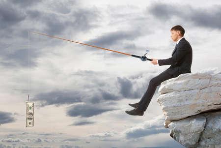 hombre pescando: Hombre de negocios joven sentado en la cima de la roca y la pesca