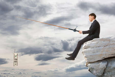 fishing: Young businessman sitting on top of rock and fishing