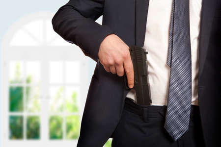 security laws: Businessman in a suit holding a gun Stock Photo