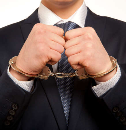confiscation: Arrested business man handcuffed hands. Close-up.