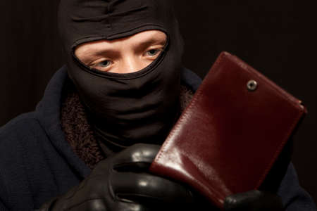 taking risks: A thief sealing from a brown leather purse Stock Photo