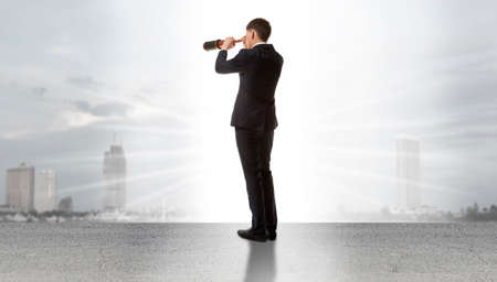 spyglass: Businessman standing on a on road and looking through a telescope at city