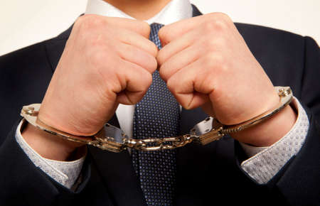 apprehension: Arrested business man handcuffed hands. Close-up.