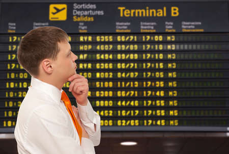 departure board: Businessman on a background of departure board at airport