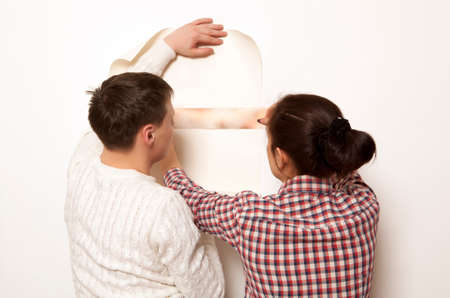 smearing: Couple putting new wallpaper in room. Repair, building and home concept