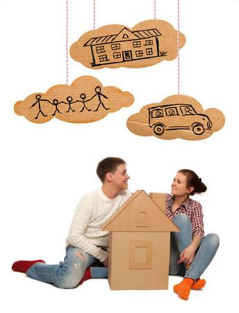 planificación familiar: Pareja joven con la casa de cartón. Fotos y plano de la mano elementos combinados
