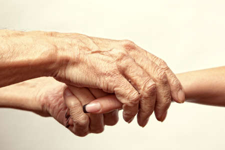 clasped: Hands of an elderly man holding the hand of a younger woman