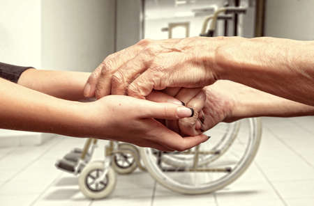 clasped: Hands of an elderly man holding the hand of a younger woman on wheelchair background