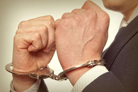 sequester: Arrested business man handcuffed hands. Close-up.