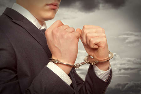 security laws: Worried caucasian middle aged businessman in handcuffs