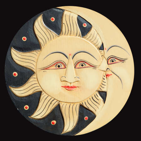 polychromatic: Sun and moon profiles, ancient carved wooden, isolated on a black background Stock Photo