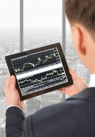 buying stock: Businessman checking the stock market on digital tablet in office Stock Photo