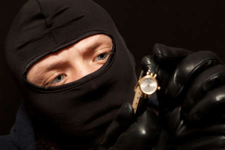 looting: Thief. Man in black mask with a golden watch. Focus on thief Stock Photo