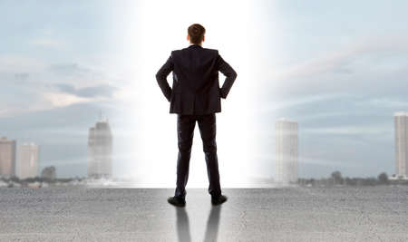 altitude: Businessman standing on a on road and looking at city