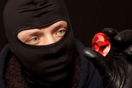 ladrón: Ladr�n. El hombre en la m�scara de negro con una gran esmeralda. Conc�ntrese en ladr�n Foto de archivo