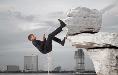 careerist: Young businessman scaling a rock   Business concept Stock Photo