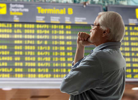 departure board: Senior on a background of departure board at airport Stock Photo