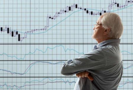 stock trader: Aged stock trader looking at monitors