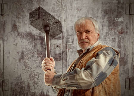 impurity: Angry old worker man holding a hammer