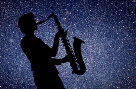 woodwind instrument: Saxophonist. Woman playing on saxophone against the background of starry sky Stock Photo