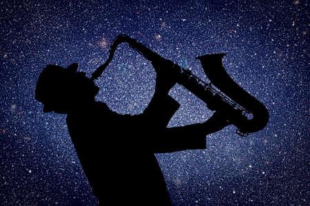 saxofón: Saxofonista. Hombre que juega en el saxofón contra el fondo de cielo estrellado Foto de archivo