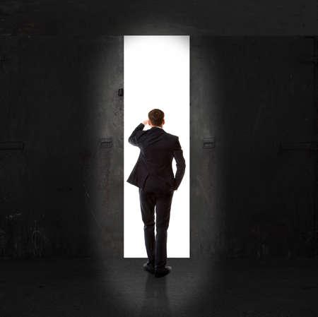 puerta abierta: Infinito. Vista trasera de un hombre de negocios de pie delante de la luz de salida Foto de archivo