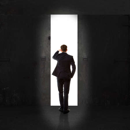 open gate: Infinity. Rear view of a businessman standing in front of the exit light