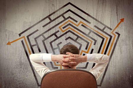 Business concept. Back view of businessman looking at a maze on wall Stock Photo