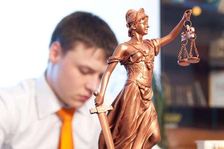 justicia: Estatua de la Justicia y el abogado de la lectura de un libro en la oficina