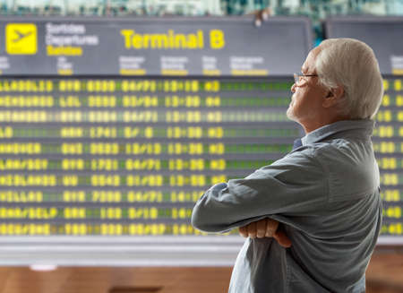 work man: Senior on a background of departure board at airport Stock Photo