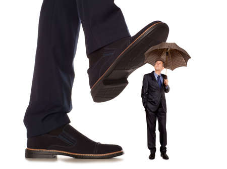 downtrodden: Cared small businessman under big leg his boss, isolated on white background Stock Photo
