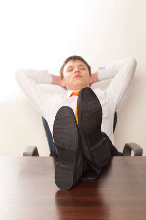 feet up: Businessman sleeping. Businessman reclining with his feet up on desk in office