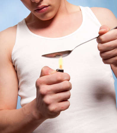 risky behavior: Man with a hardline drug addiction heating drugs in a spoon over a flame